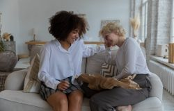 Women sitting on a couch having a casual conversation and smiling.